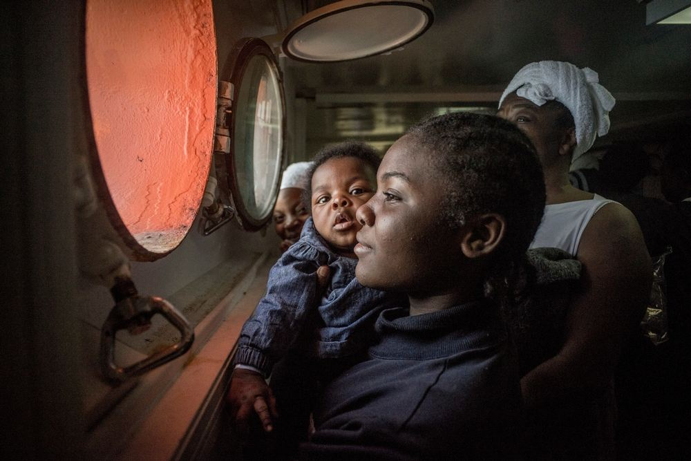 A woman and her baby look out of a porthole of an MSF search and rescue ship, run in cooperation with SOS Méditerranée, off the coast of Libya. Photographer: yann Merlin/SOS MEDITERRANEE