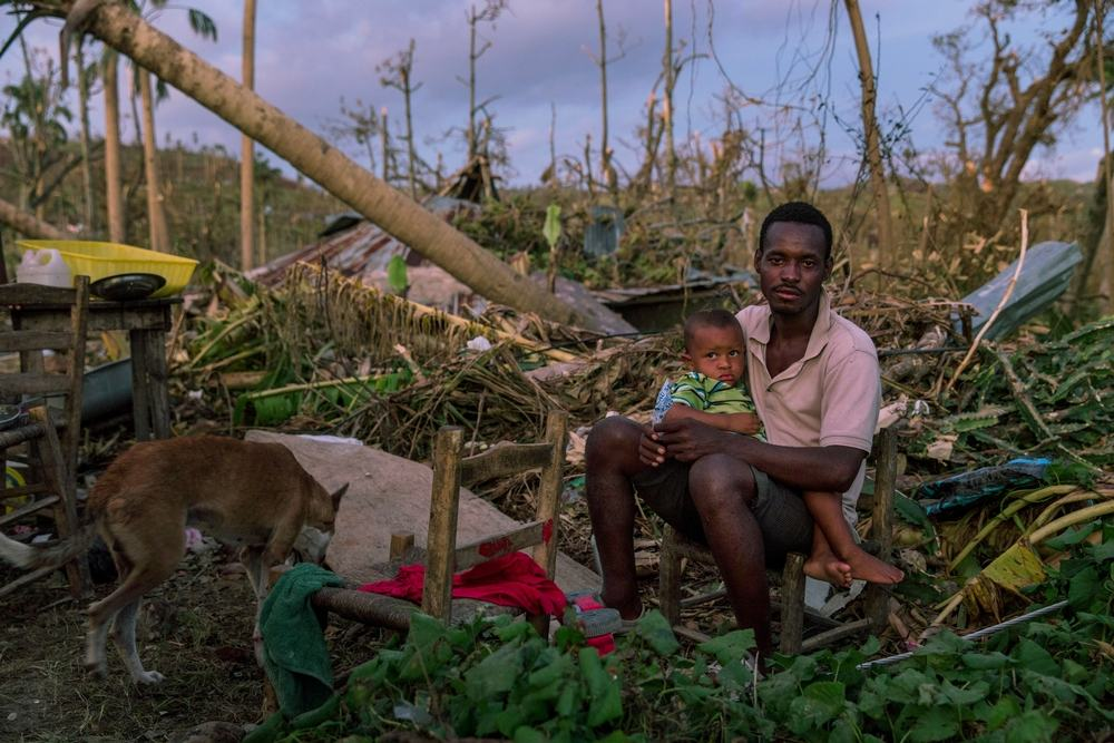 A man sits with his son, in the remains of their home, near Port Salut, in southwestern Haiti. Hurricane Matthew tore through the Caribbean on 4 October devastating large parts of the island. MSF teams used every means of transport, including donkeys, to bring medical aid to some of the more remote communities in the mountains, cut-off by damage to bridges and roads. Photographer: Andrew McConnell/Panos Pictures