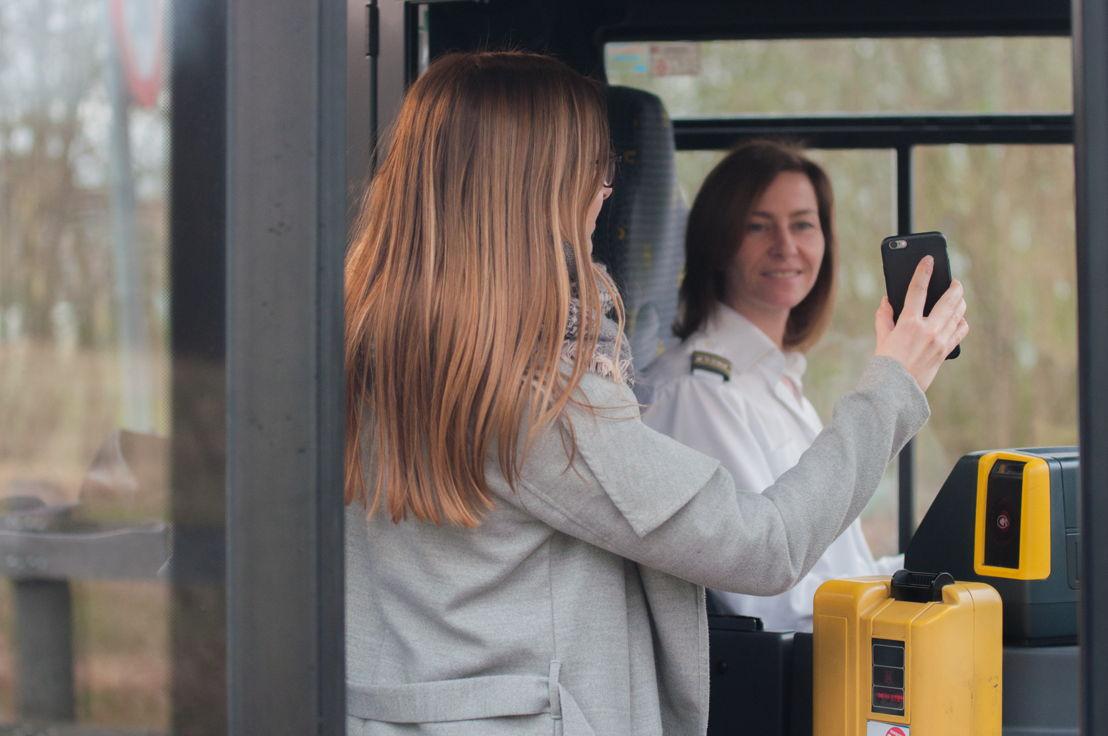 Een vrouw toont haar digitale vervoerbewijs aan de chauffeur.