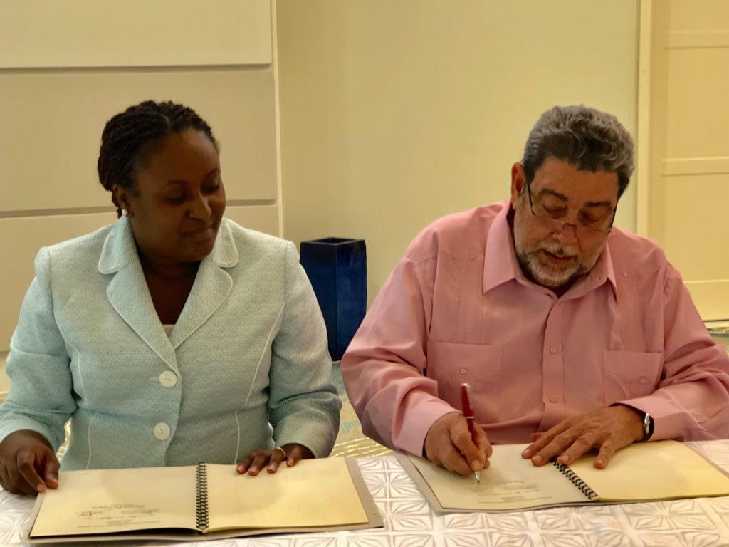 Incoming Chairman of the OECS Authority, Dr. Hon. Ralph Gonsalves, and Internal Auditor for the OECS Commission, Mrs. Mauricia Carr, sign Terms Of Reference for the OECS Audit Committee.