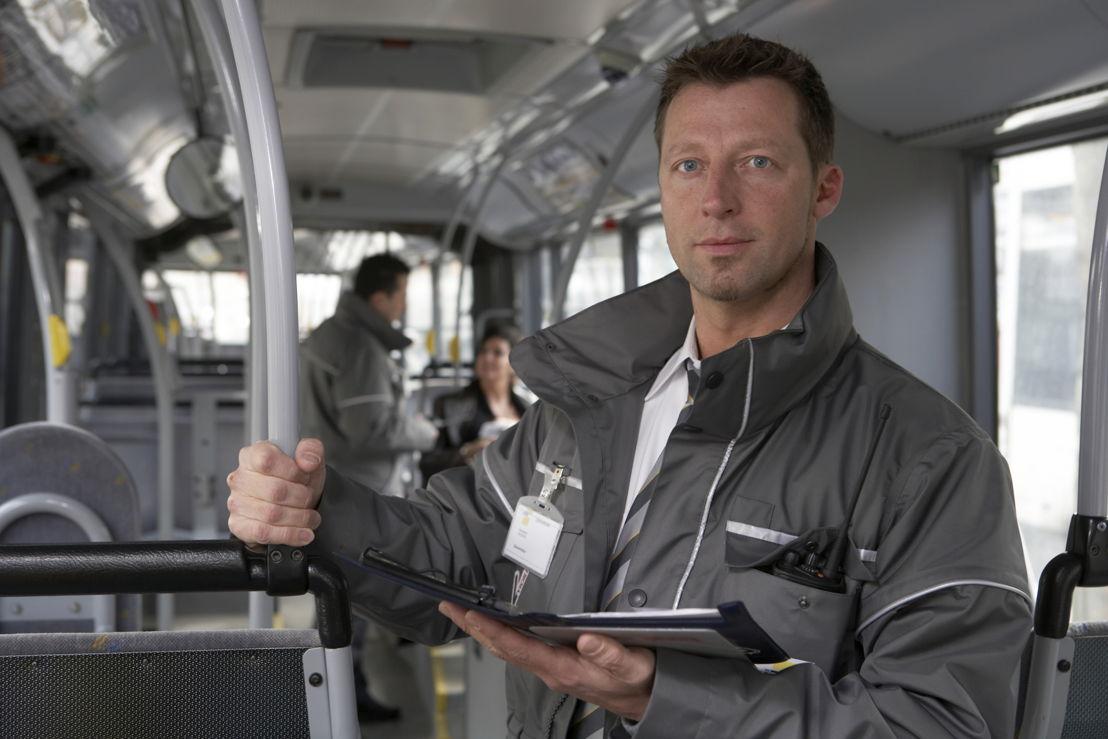 Een controleur van De Lijn, herkenbaar aan het grijze uniform en het Vigilis-logo.