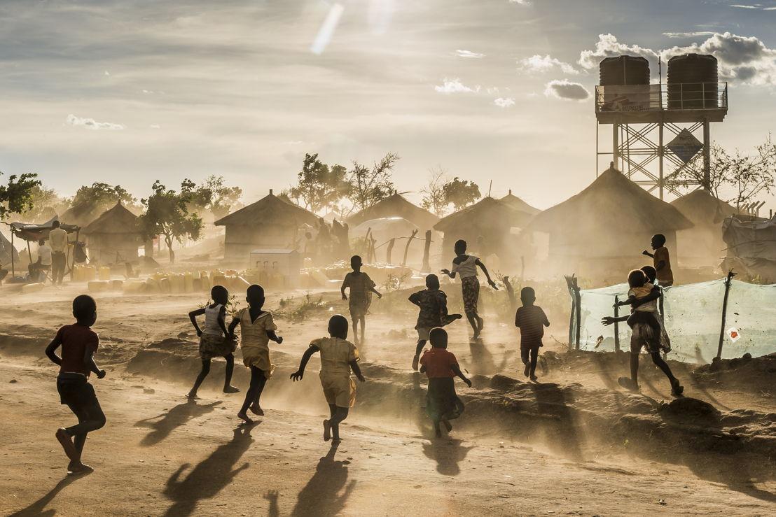 Kinderen spelen in Bidi Bidi kamp. Op de achtergrond een watertoren en tenten © Frederic Noy