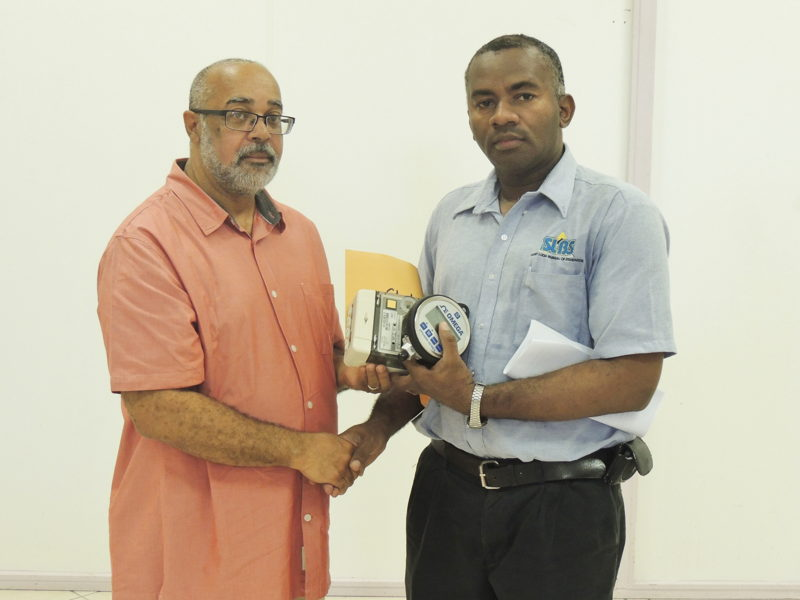 Mr. Gittens accepts equipment from OECS Director General - Dr. Didacus Jules