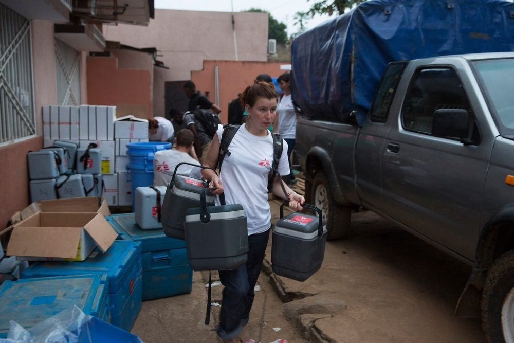 A Medecins Sans Frontieres (MSF) staff member carries cold boxes containing yellow fever vaccines on the first day of the vaccination programme in Matadi, DRC. Photographer: MSF