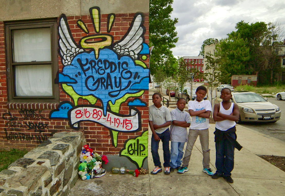 Boys in Baltimore with a tribute mural to Freddie Gray