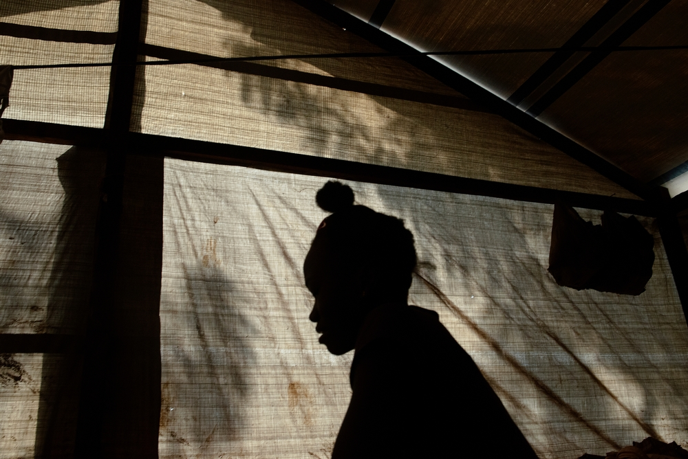 MSF159659<br/>Rebeka inside shelter at a displaced persons camp in Benzvi, Bangui.<br/><br/>Rebeka fled the violence in Kaga-Bandoro, a market town 245 km North of Bangui. Her house there was burned and looted by armed groups. After five days travelling from Kaga-Bandoro to Bangui, she arrived in BenZvi camp with her older brother and older sister. It&#039;s now been five months since moved to the camp. She does not work but cares for her sisters children: &quot;The hardest thing for us is to find food. Sometimes we sleep without eating&quot;. Rebeka says she does not want to go back to Kaga-Bandoro, and wants to remain in the camp for more security.