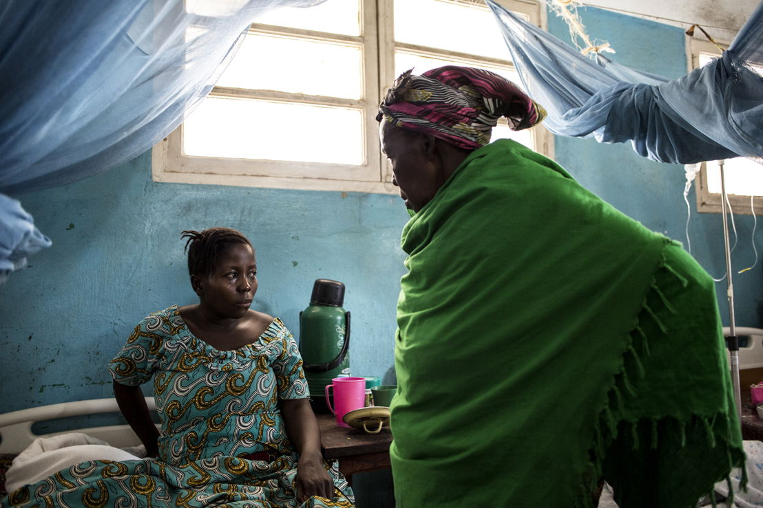 Denise Borive (31) (R), speaks with her mother as she recovers from an emergency caesarian in a hospital room on 2 March 2018 in Bunia. After hearing about a pending attack on her village she fled on foot with her mother and children at nine months pregnant to seek safety. ©John Wessels/MSF