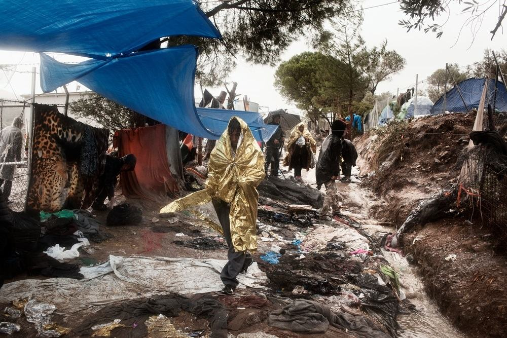 Photographer: Alessandro Penso<br/><br/>Caption: Refugees and migrans walk along a muddy path, lined with rubbish as they wait to be registered at the Moria Reception Centre in Lesbos, Greece.