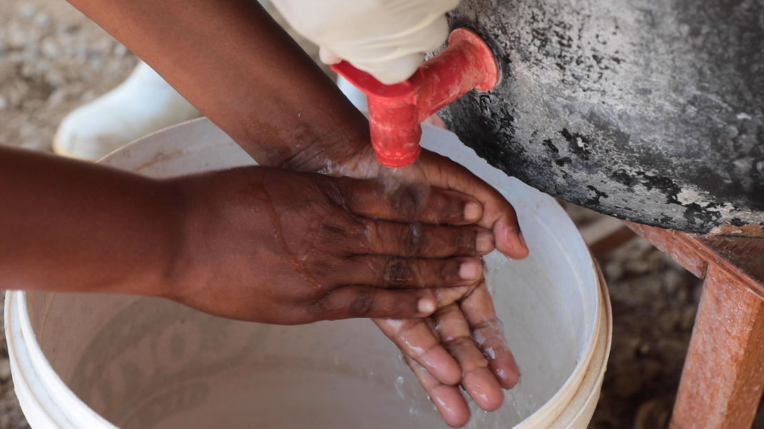 A suspected cholera patient washes hands for infection control purposes at the Glenview Cholera Treatment Centre, Harare. As part of the current cholera response in Harare, MSF mentored nurses to manage patients and sprayers for infection control. Infection control is an important aspect of preventing the spread of cholera. Photographer: Marion Mossing