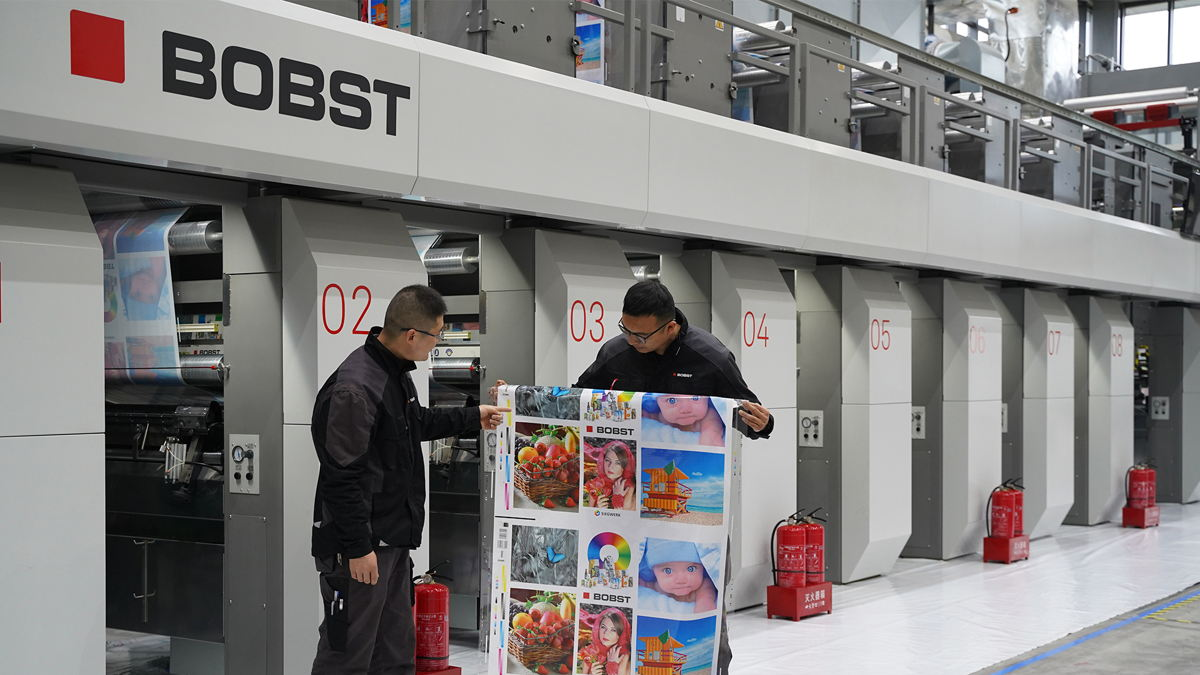 Messrs Shuhui Sun (right) and Bo Zhang (left), process engineers at Bobst Changzhou, examining the technical print sample printed with Siegwerk water-based inks in Bobst (Changzhou) Competence Center.