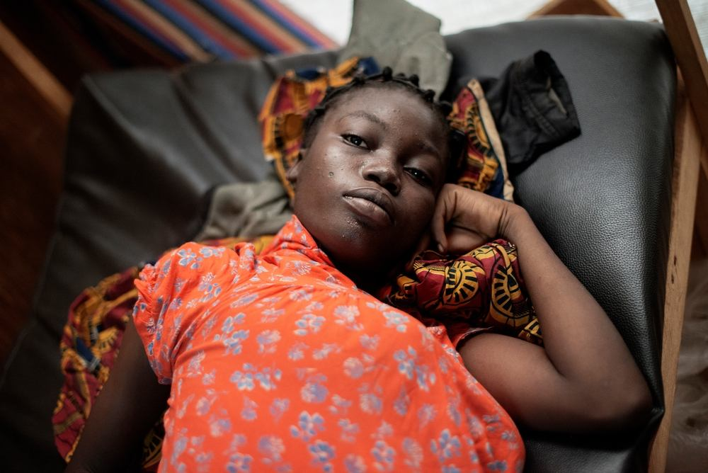 MSF159683<br/>16 year old Naomi waits to be seen at a Medecins Sans Frontiers (MSF) hospital at a displaced persons camp in M&#039;Poko, Bangui.<br/><br/>Naomi will give birth to her first child at the MSF maternity ward in Mpoko camp. When her father died, Naomi was sent by her mother to study in Garoua Boulai in Cameroon, where some of their family members live. This is where she met the father of her child. To be with her family when the baby arrives, Naomi travelled for nearly a month to reach Bangui. The whole family, including her grandmother, her aunts and her mother, gathered in the MSF hospital to await the arrival of the baby.