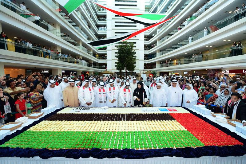 سمو الشيخ  أحمد بن سعيد آل مكتوم يقطع قالب حلوى خلال الاحتفال باليوم الوطني الـ45 في المقر الرئيس لمجموعة الإمارات. وفي الصورة عدد من كبار مسؤولي المجموعة.