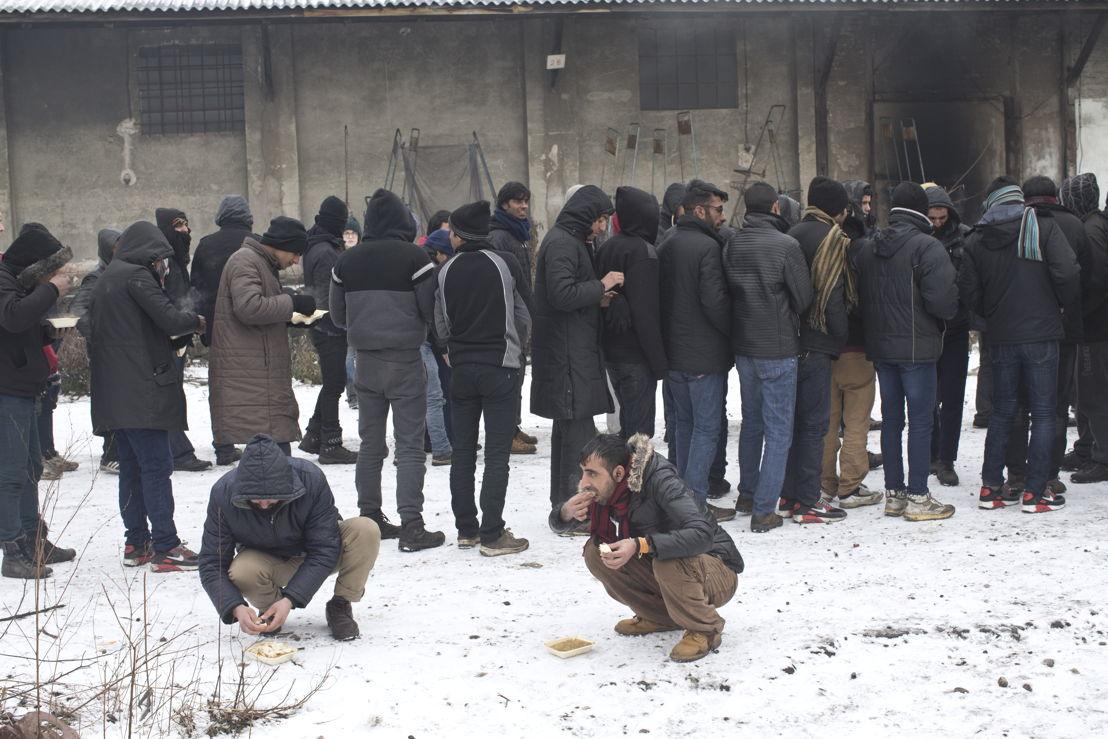 Vluchtelingen wachten op voedsel in een oud magazijn in Belgrado © Marko Drobnjakovic