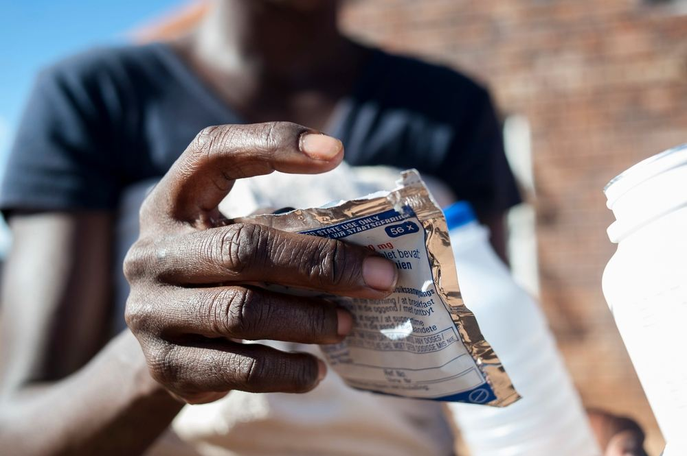 A woman holds a packet of pills at an activist meeting in Soshanguve, a township outside of Pretoria on April 16, 2015. Photographer: Stefan Heunis