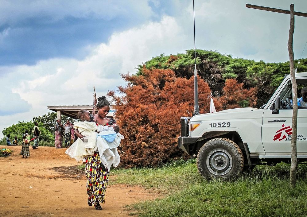 A mother carries her two children to Tchabi health centre to receive polio vaccinations during a community healthcare and health promotion programme run by MSF in Boga, Democratic Republic of Congo. Photographer: Gabrielle Klein/MSF