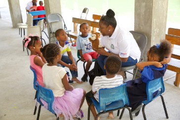 OECS Commission Staff reading to students as part of the USAID/OECS ELP