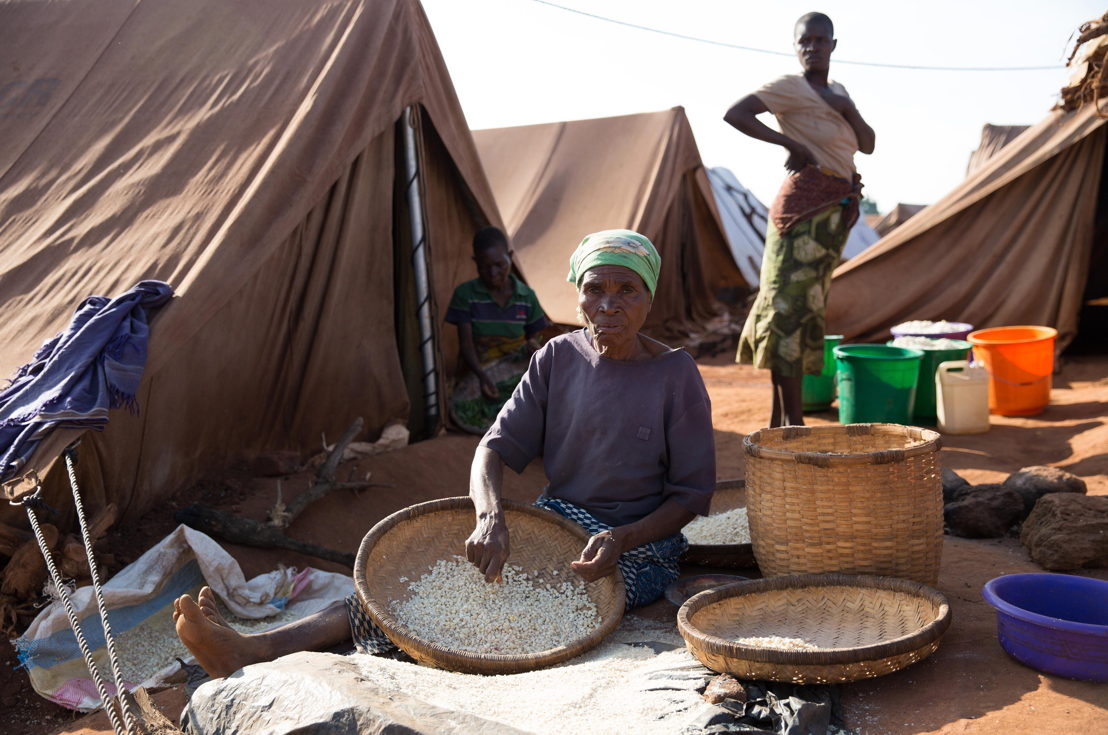 A woman prepares maize in the Kapise 2 settlement. Over 5.800 Mozambican nationals have camped in the village of Kapise 2 in Malawi after fleeing their homes in Mozambique, the majority of them women, children and the elderly. They are living in precarious conditions well below internationally recognized humanitarian standards. © James Oatway / MSF