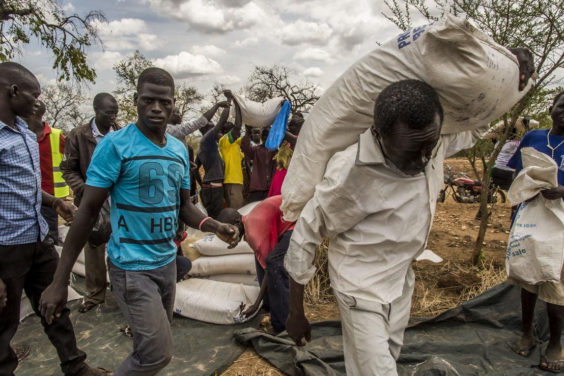 Des réfugiés récupèrent des rations de nourriture attribuées à un groupe de plusieurs familles. Ils prennent les sacs, s'installent dans un coin et se les répartissent © Frederic Noy