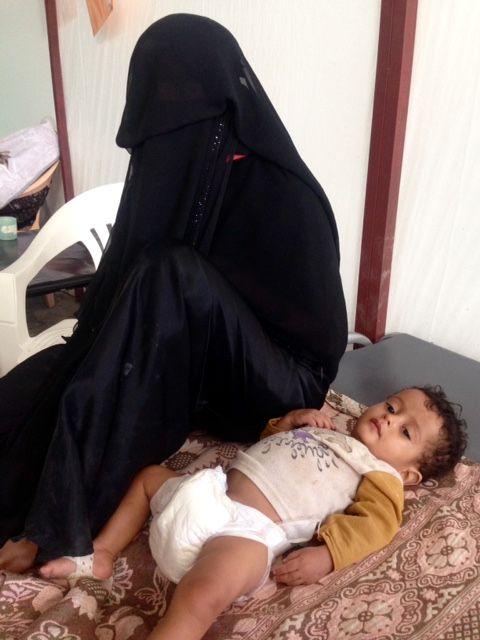 Fatima est assise sur le lit à côté de son fils Ishaq, âgé de 18 mois. Il est soigné dans l'un des centres de traitement du choléra de MSF à Kilo, dans le sud du gouvernorat d'Ibb. Le coût du carburant a considérablement augmenté depuis l'instauration d'un blocus par la coalition dirigée par l'Arabie saoudite en novembre et Fatima ne peut pas payer les frais de transport à destination et en provenance de l'hôpital. 16 novembre 2017 ©MSF