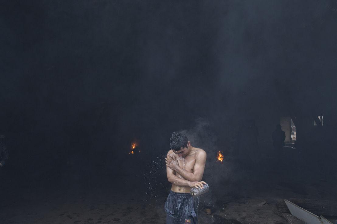Ein Mann wäscht sich mit heissem Wasser ausserhalb eines stillgelegten Eisenbahnlagers, das von Flüchtlingen und Migranten als vorübergehende Unterkunft in Belgrad genutzt wird (Foto: Marko Drobnjakovic).