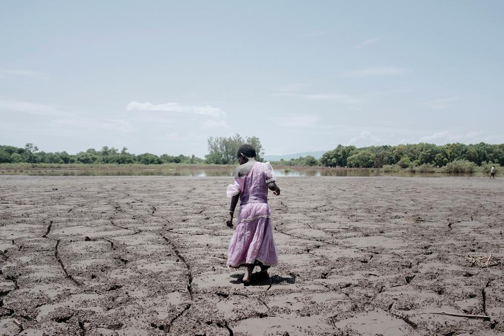 System identifier<br/>: MSF141951<br/>Title<br/>: Malawi floods, FEB 2015<br/>Photographer / cameraman<br/>: Luca Sola<br/>Countries:<br/>Malawi<br/>Description<br/>: Alesi Phiri, 7yo, walks on a former field as she looks to the thick coat of dried mud. 85%<br/>of the population in the area relies on agriculture for economic survival. Consequences of the floods<br/>will likely be felt for months as all crops have been destroyed.