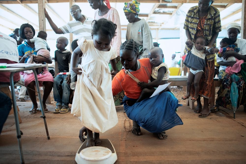 A child is weighed at a Medecins Sans Frontiers (MSF) hospital at a displaced persons camp in M'Poko, Bangui. Photographer: Luca Sola