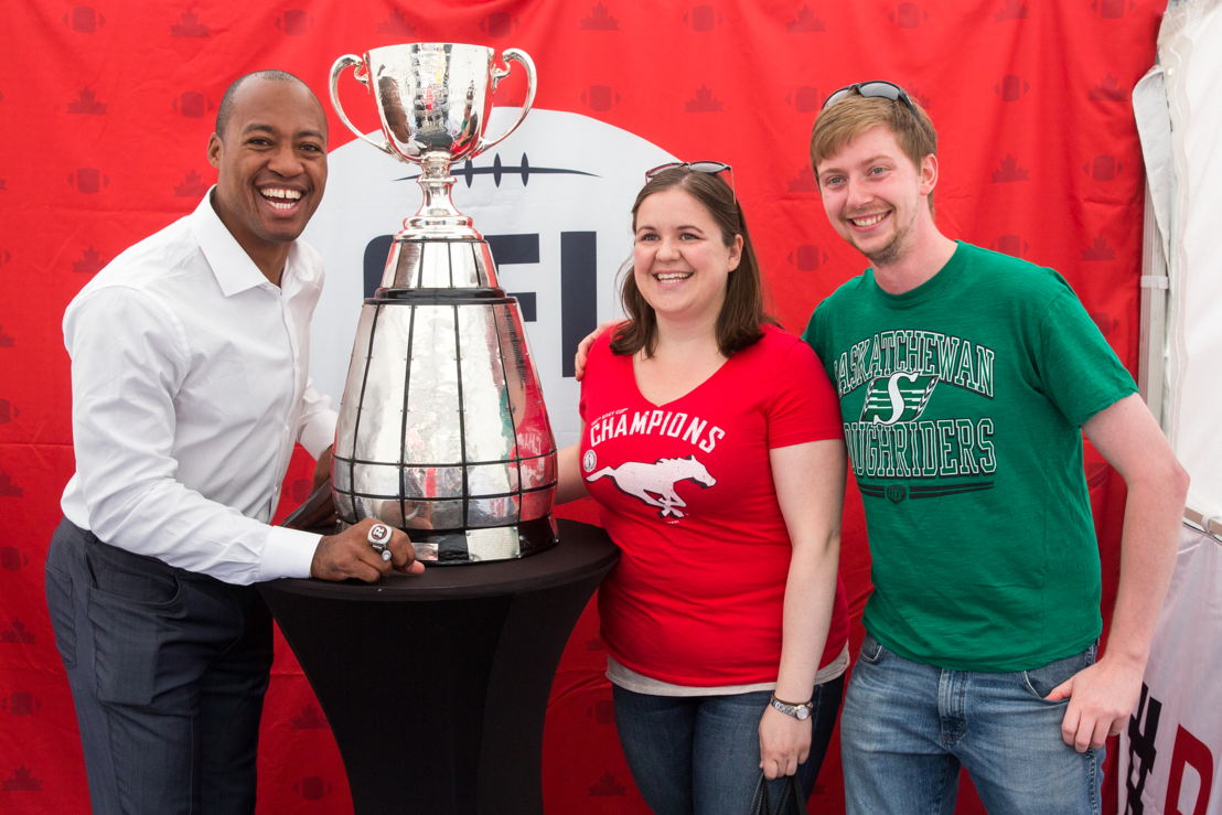Henry Burris poses with two CFL fans and the Grey Cup. Photo Credit: Jim Ross/CFL