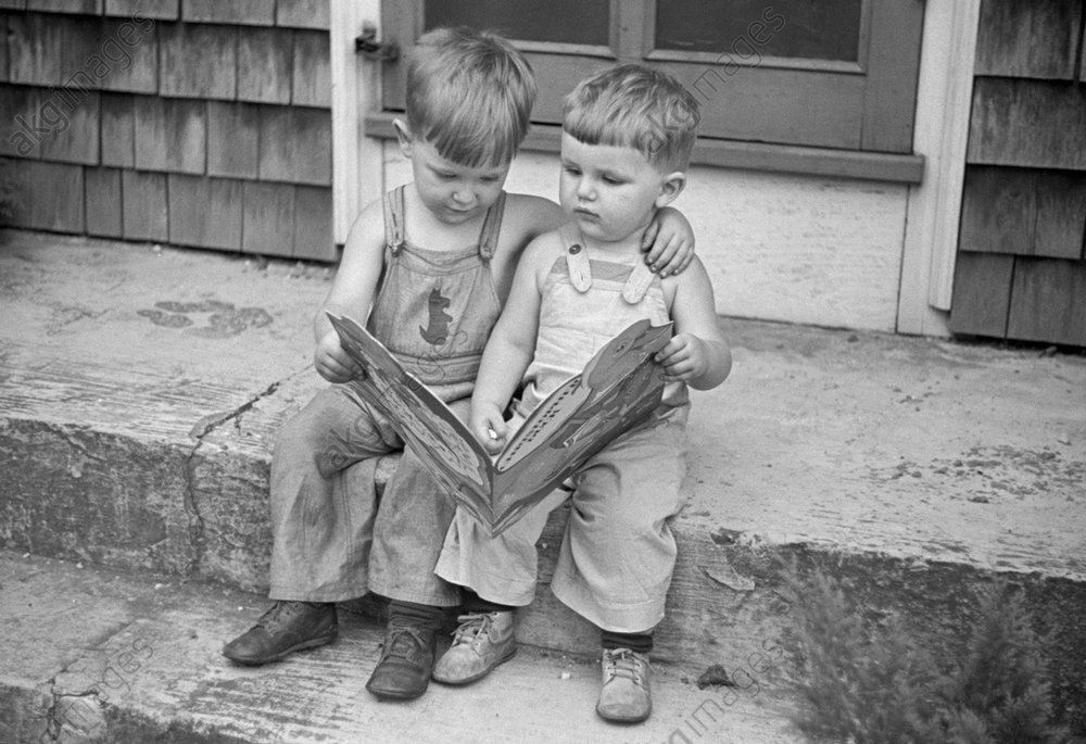 Two little boys (brothers / twins) sitting on the front steps of a house, reading &quot;Christopher Duck&quot; by Eleanora Madsen<br/>together.<br/>Photo, 1938.<br/>AKG1035920