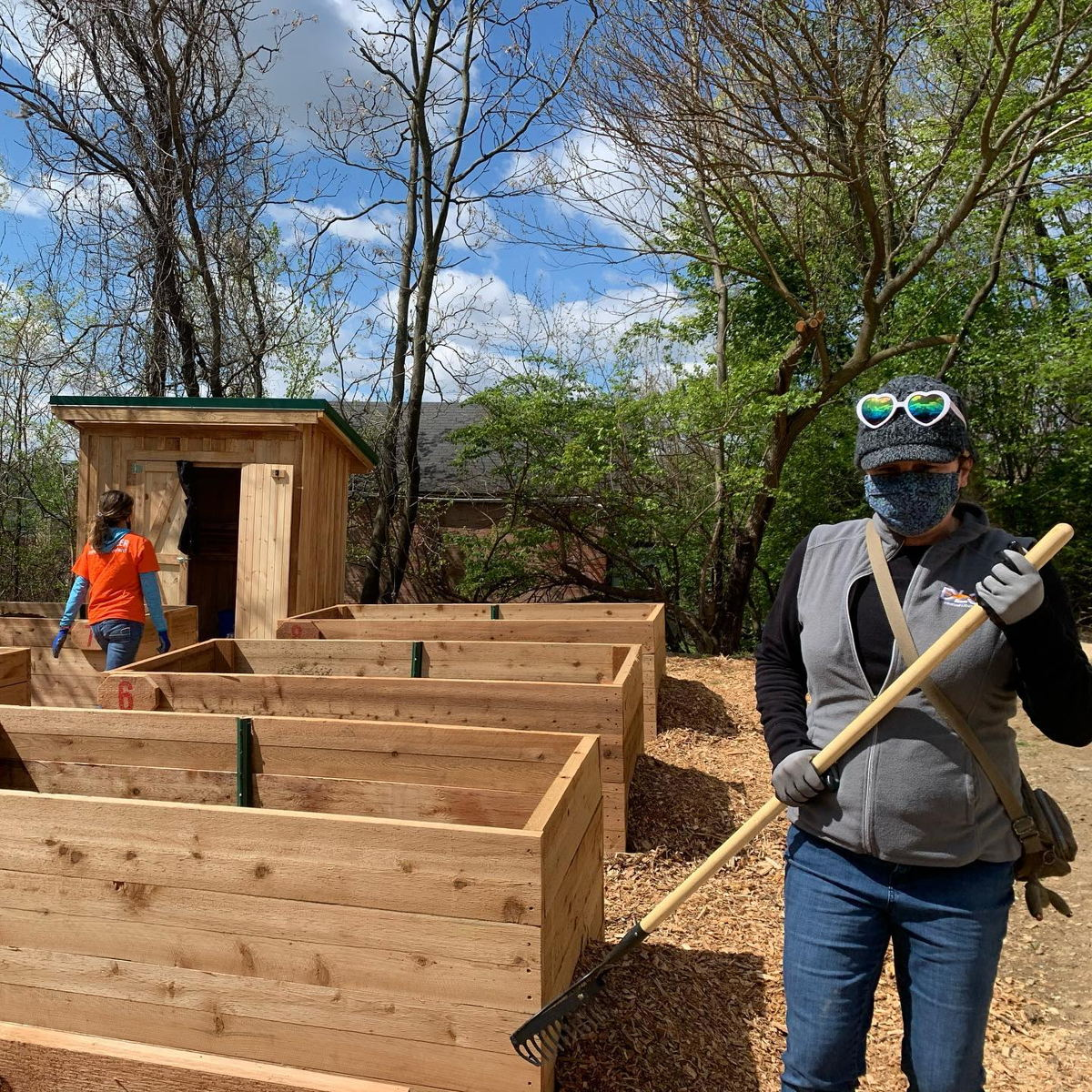 DLC volunteers lay woodchips near large planter boxes at Sunny