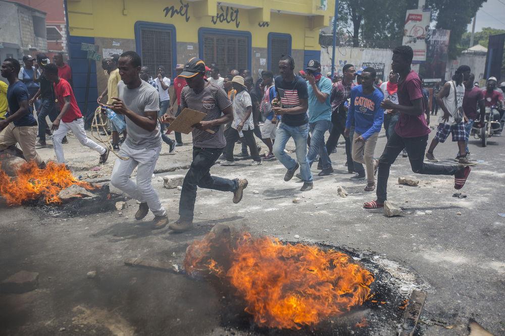 Manifestantes corren cerca de neumáticos en llamas durante una protesta en Puerto Príncipe el 9 de junio de 2019. © Jeanty Junior Augustin/MSF