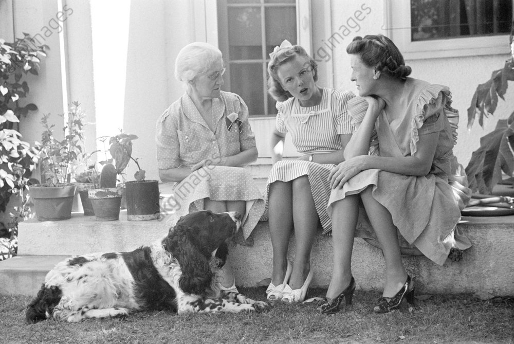 Three generations of women sitting on the back porch, talking (young blond woman in the centre is Barbara Bradford Mann).<br/>Photo, 1940.<br/>AKG1013671