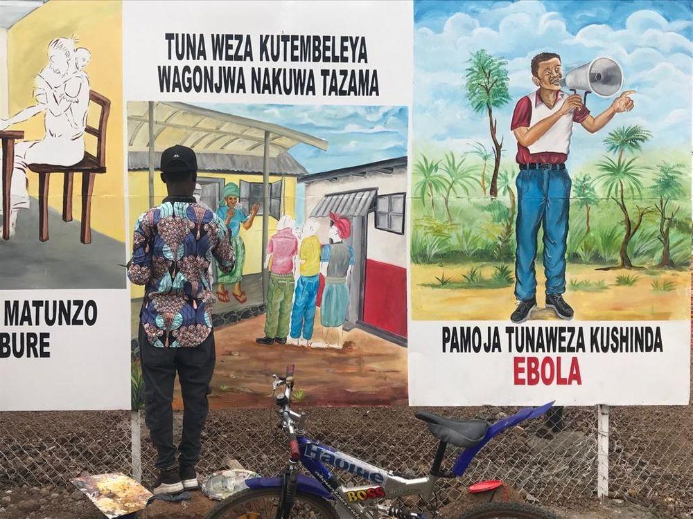 Artistas locales pintan en la valla del nuevo Centro de Tratamiento del Ébola en Munigi, Goma, para ayudar a concienciar sobre la epidemia a las comunidades locales.  © Jinane Saad/MSF