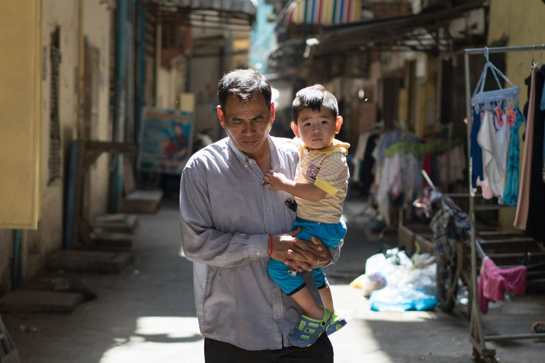 Cambodia Hep-C. Din Savorn, 50, carries his son to daycare in Phnom Penh, Cambodia, 20, April 2017. In 2016, MSF set up a treatment clinic for patients with hepatitis C in Preah Kossamak Hospital in Phnom Penh.  By April 2017 over 10,000 patients had been screened since the start of the programme, of whom 4,000 patients had been diagnosed with hepatitis C infection.  Around 800 patients have, as a result, been put on treatment since October 2016. MSF is treating patients with the improved hepatitis C medicines called direct-acting antivirals (DAAs) that have recently been introduced. These medicines are far more effective than previous hepatitis C drugs; they carry far fewer side-effects for patients and the treatment lasts around 12 weeks compared with the previous treatment of 24 to 48 weeks with painful weekly injections. However the high price of the medicines is a barrier to treatment access. Diagnostic costs too present a challenge for treatment providers. Photographer: Todd Brown