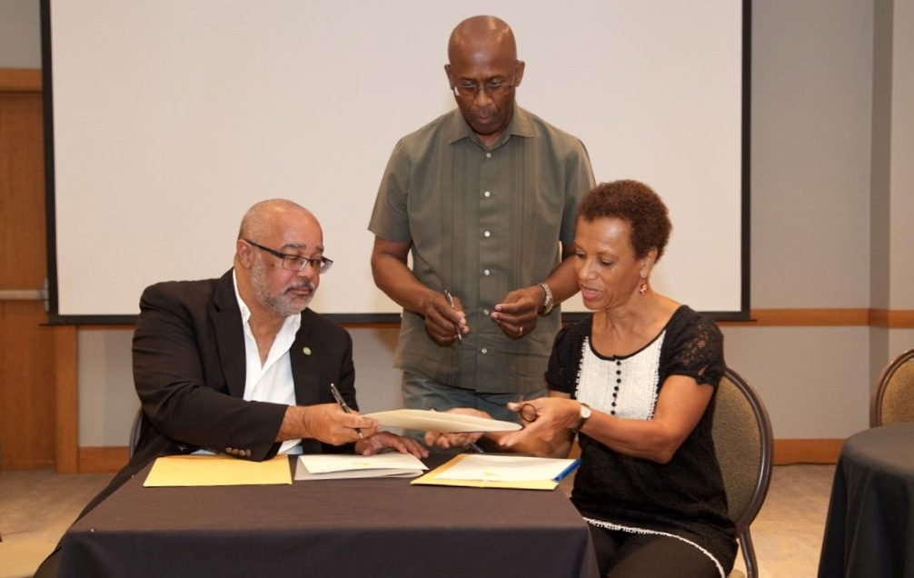 OECS Director General, Dr. Didacus Jules, and Professor Jessica Byron, Director of the UWI Institute of International Relations, complete MOU signing.