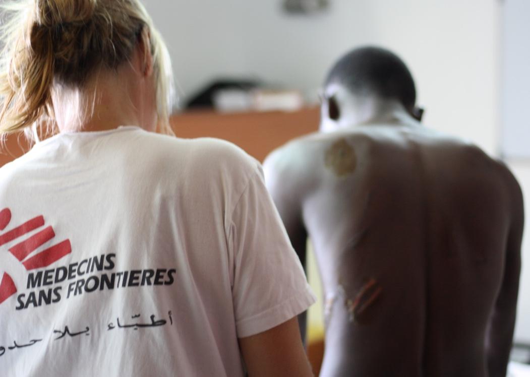Een verpleegster van AZG aan boord van MV Aquarius verzorgt een patiënt uit Nigeria met wonden door marteling