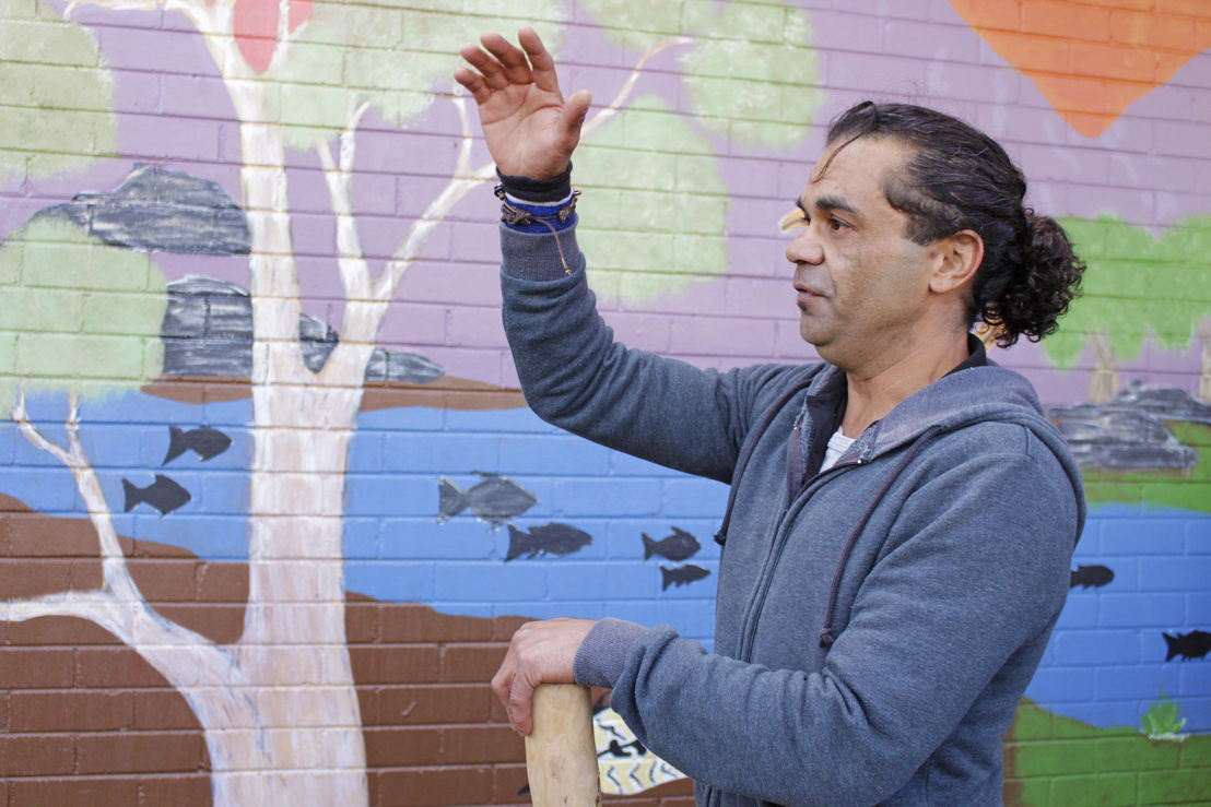 Artist Daniel Williams in front of one of the murals in Canberra. Image: Adam Spence, ANU.