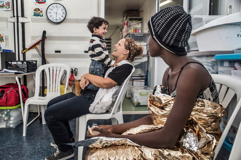 Photographer: Francesco Zizola<br/><br/>Caption: Doctors Without Borders (MSF) nurse Line Lootens entertains a small child on board the Bourbon Argos following a rescue in the Mediterranean The refugees will be taken to Italy.