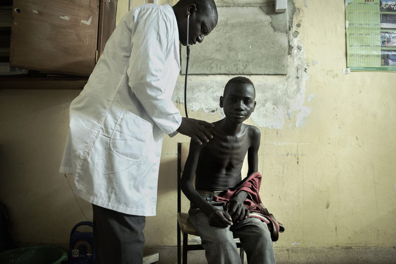 """Simbazako Thove, 19 years, who has HIV and TB is prepared for an X-ray in the X-ray room, Nsanje district hospital. <br/><br/>Simbazako was forced to leave school due to financial problems. He lost both parents and now stays with his elder brother who is a small scale farmer. He has had two previous chest X-rays in Nsanje hospital, and has come again due to pains in his chest.<br/>Simbazako, who came alone, tested HIV positive last year and takes his antiretrovirals regularly. He had heard about HIV and because he was continually sick, decided to for an HIV test. Members of his local church sometimes support him, but he can go a day or so without food sometimes. His sister lives far away.<br/><br/>Simbazako says """"I feel too much pain in my ribs. I take my ARVs without skipping even a day but my health is not improving as I had expected."""" <br/><br/>Through the Nsanje HIV TB District Support programme, MSF is working with medical teams in Nsanje district hospital to improve diagnosis and clinical care of AIDS, including imaging, laboratory and pharmacy support. Photographer: Luca Sola"""