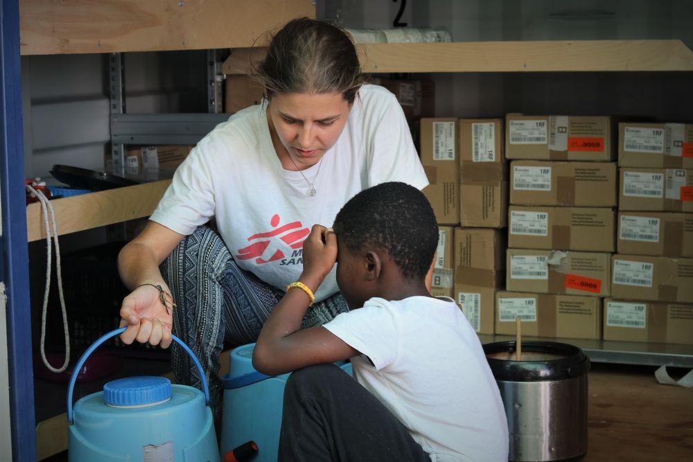 Stefanie, responsable del equipo médico de MSF con uno de los niños por el Ocean Viking.  Hannah Wallace Bowman/ MSF
