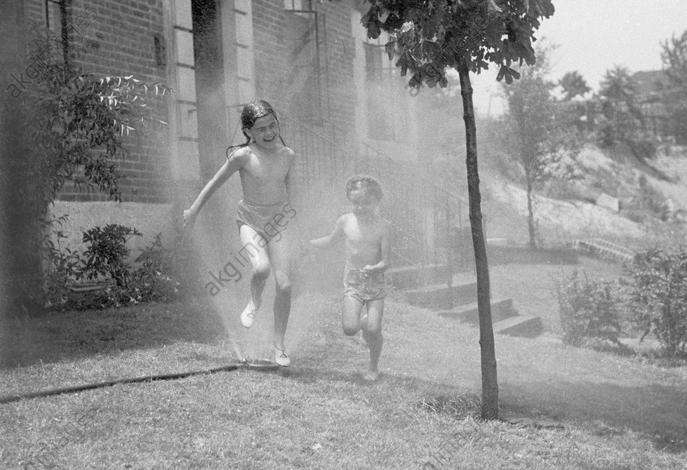 Two sisters running through garden sprinklers, New York.<br/>Photo, 1939.<br/>AKG1045961