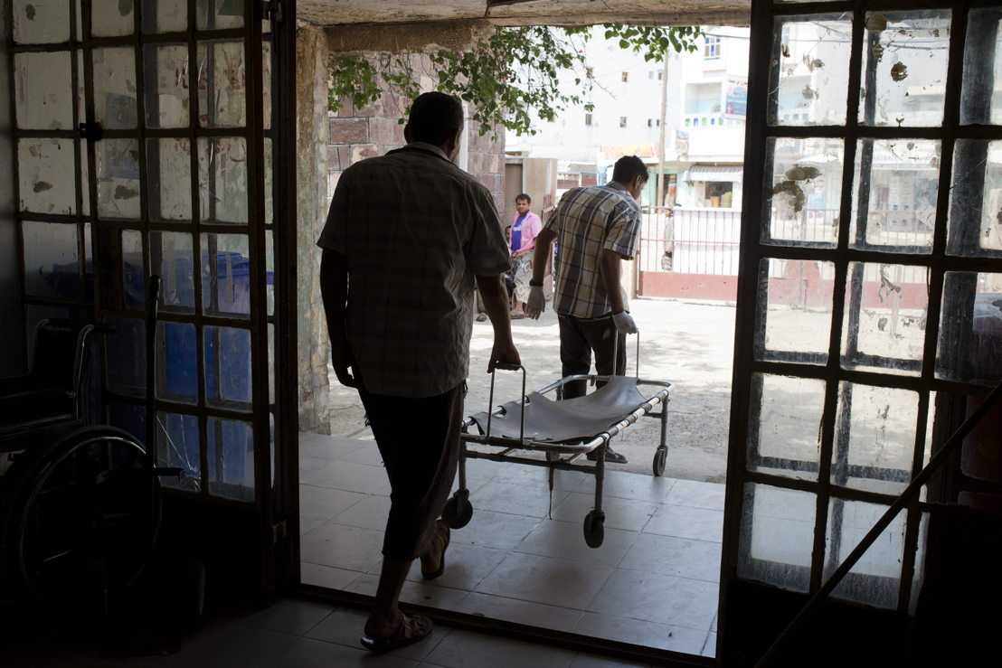 Two Yemeni men carry a stretcher out of Al Salam Hospital to go pick up a patient on July 22, 2015 in Qataba, Al Dhale governorate, Yemen. Credit MSF.