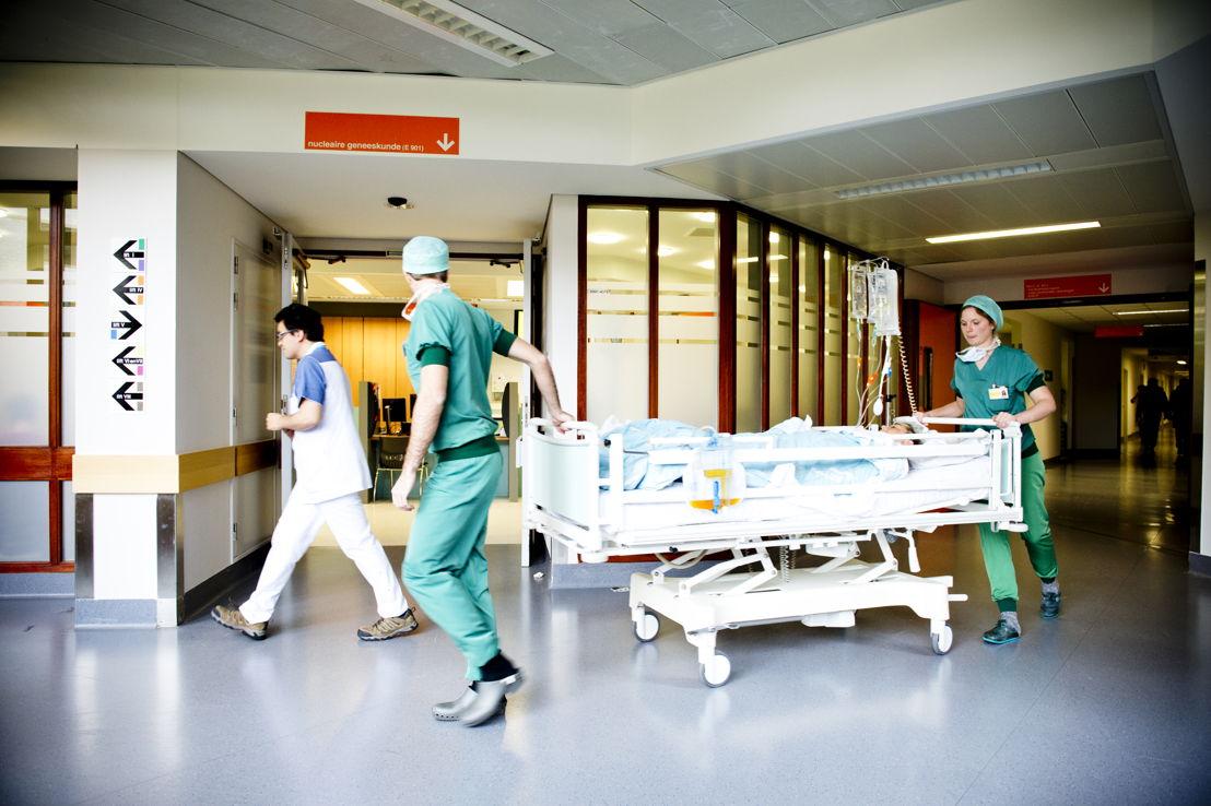 Medewerkers brengen een patiënt van de operatiezaal terug naar de kamer