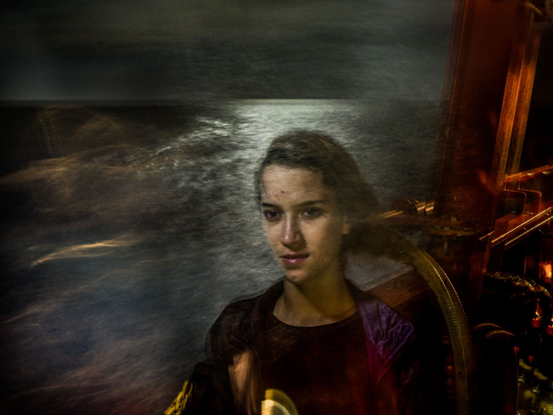 "The Crossing 05. &quot;The Crossing&quot; is a photographic project by Andrew McConnell/Panos Pictures based on night portraits and testimonies from people rescued by the SAR Prudence boat in International Mediterranean Sea waters in July 2017.<br/><br/>CAPTION / DESCRIPTION:Omayma, Morocco, 21<br/><br/>I had a lot of problems with my father, as did all my siblings. There are four of us, with me in the middle. My father's a drug addict. He didn't give us money to go to school, so we dropped out. He had no job. Although he was healthy, he'd sleep at home all day, so my mother worked as a housekeeper to feed us. He used to beat my mum with a belt, over and over until she bled. He'd come home and beat us all with anything within reach. <br/><br/>One Friday, my dad was drunk and asked me to get him some money by any means I could, even if it meant prostituting myself. Again and again he pulled my hair, pushed me around and banged my head against the wall until my nose bled. The drugs had made him mad. My mother and I were under such stress that we used to faint a lot. When I told my mum we should call the police, she got angry and said we should be patient. She said if we reported him, we'd all be out on the street as the house was his. <br/><br/>When I told my mother I wanted to go to Europe, she was sad and tried to stop me. She asked me how I could leave her when she was sick. She said I should stay and find a job and maybe get married. But I'm too young to get married. I asked her for money for the journey and promised that I'd return it once I'd educated myself. She was worried I'd die. ""What will I do if you die?"" she asked me. I replied that if I died, she should forgive me. <br/><br/>I flew to Tunisia and took a bus from Tunis to my uncle's house near the border. I couldn't stay with him because he can barely feed his own children. We talked with people who could put me on a boat to Europe. The smuggler took me to a house in Sabrata [on the Libyan coast, 100 km east of the Tunisian border] with other women and young men and we stayed there for a couple of months. They beat the men, but the girls were well treated. <br/><br/>I paid them 20,000 Moroccan dirhams [1,800 euros] – mum borrowed the money from the family she works for. One night they came to us and told us to collect our things quickly because it was time to go. When I took the boat I saw death with my own eyes. There was 20 cm of water in the bottom of the boat. There were a lot of young kids, I couldn't even lift my head because I was so seasick – I threw up many times. <br/><br/>They gave us lifejackets, but they turned out to be fake. When we found out, the young men in the boat – Moroccans and Syrians – started arguing and fighting. The women and children were terrified we'd capsize. The sea is very dangerous. I'll never take a boat like that again. <br/><br/>I thank God that no one assaulted me and that I was saved. I will continue my education. I will learn a new language and find a job. I want to help my mother, because otherwise she'll work as a housekeeper forever. My father will carry on doing nothing. I couldn't go back to Morocco, I'd rather die. Photographer: Andrew McConnell"