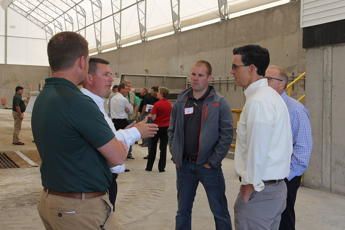 Troy Koehler (second from left) talks with Benton County Farm Bureau president Dustin Schirm (center) and Iowa Farm Bureau members in the dry fertilizer facility.