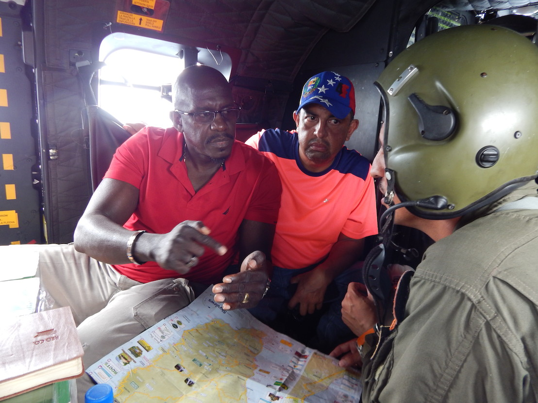 Grenada's Ambassador to the OECS H.E Dr. Patrick Antoine discusses food drop logistics mid flight on the way to Dominica. Photo credit: Janeka Simon