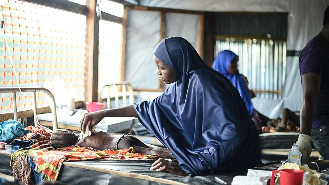 Een moeder legt een koud washandje op haar kindje om de koorts te doen zakken terwijl het uitrust op bed in de isolatiekamer. Tienduizenden mensen zijn op de vlucht voor het geweld van Boko Haram in Borno State, Nigeria ©Ikram N'gadi/MSF