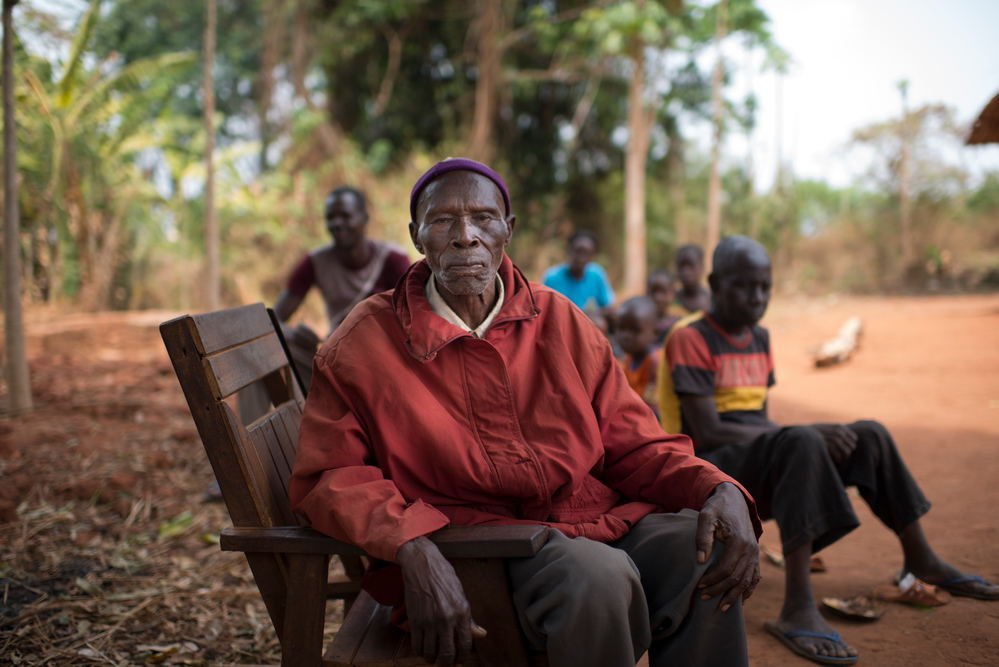 """Henri Passendro, 84, chief of Nasima village, left Nasima on 6 Decembre 2016 with his family to find shelter at Aviation IDP camp. """"The were infighting between UPC and FPRC near the village, a rumour said they were burning villages, so we fled. My son went back later to see what was left. All had been burned down. I would like to go back to my village, but I have no money left to pay transportation"""". His son provides for Henri's survival. Photographer: Colin Delfosse/Ouf of Focus"""