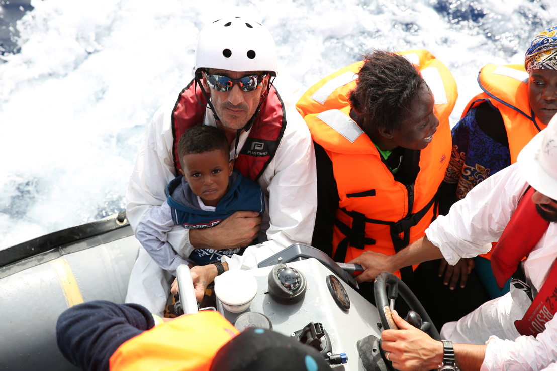 A member of the crew holds a little boy on 16 October. A large number of the rescued people are minors. They often sit along with the mothers in the middle of the flimsy boats, so if a crack appears they are in the most vulnerable position. Photographer: Mohammad Ghannam