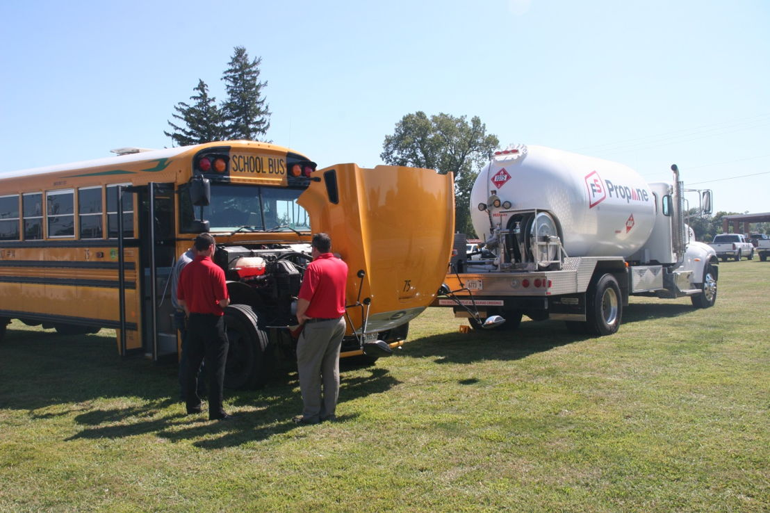 Prairieland FS employees examine a new propane autogas engine installed in a school bus.