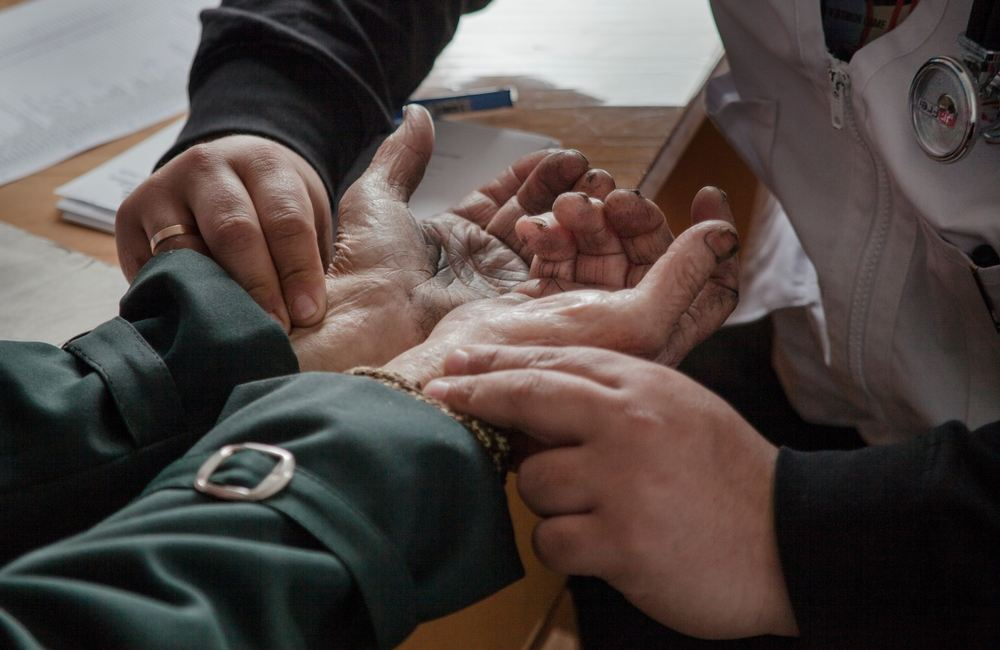 System identifier: MSF145431<br/>Title: Mobile Clinic in Gorozishe, Lugansk<br/>Photographer / cameraman: Jon Levy<br/>Countries: Ukraine<br/>Description: Dr Moshin Mehraj checks the pulse of an elderly patient at the MSF mobile clinic in the village of Gorodishe, near Lugansk.